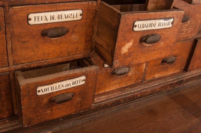 mobilia di legno con i molti cassetto nei wi della drogheria fotografia stock