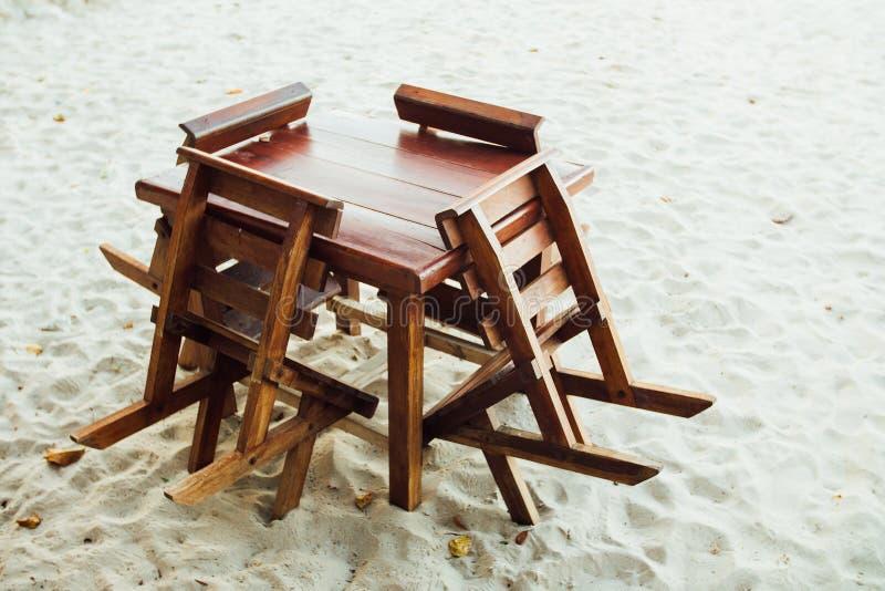 Mobilia di legno sulla spiaggia sabbiosa Supporto delle sedie e della Tabella sulla spiaggia di sabbia immagine stock libera da diritti