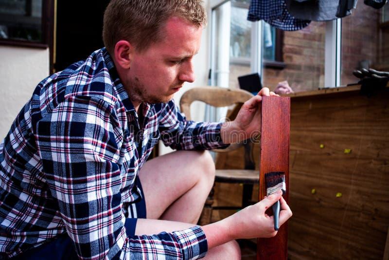 Mobilia di legno vecchia di verniciatura La governante dipinge i bordi di legno con il pennello Concetto di rinnovamenti e di mig fotografia stock libera da diritti