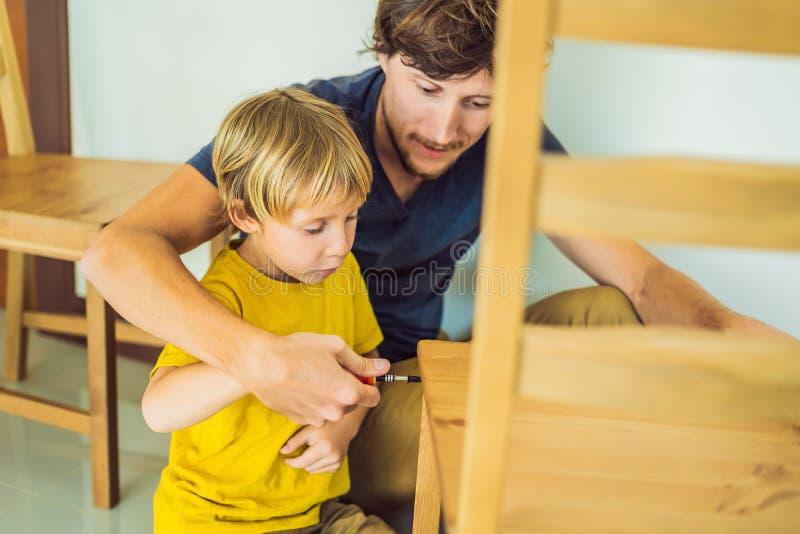 Mobilia di montaggio del figlio e del padre Ragazzo che aiuta il suo papà a casa Concetto 'nucleo familiare' felice fotografia stock
