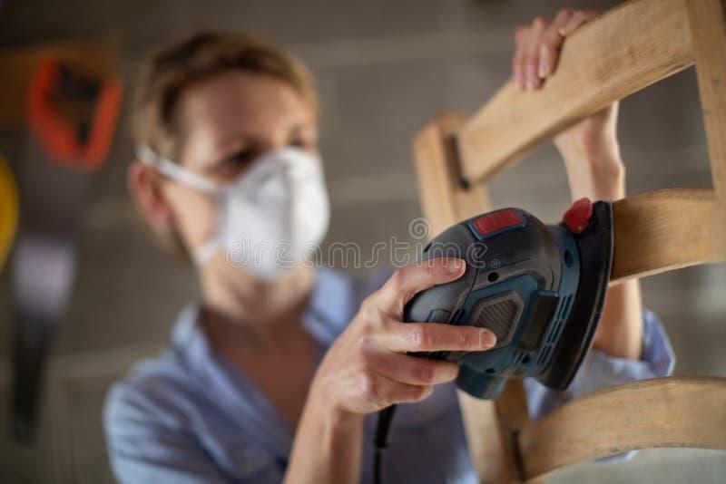 Mobilia matura di Upcycling della donna in officina a casa facendo uso della sabbiatrice elettrica immagini stock libere da diritti