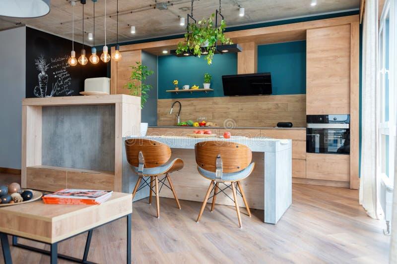Mobilia moderna in cucina di lusso Interno scandinavo minimalista in appartamento del sottotetto con mobilia di legno, lampade immagine stock libera da diritti