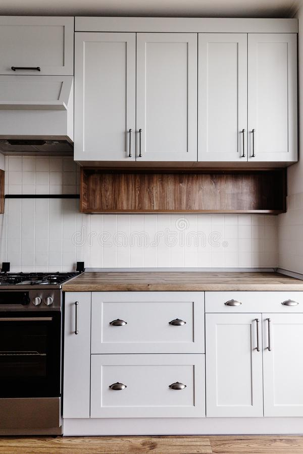 Mobilia moderna di lusso della cucina nel colore grigio e maniglia d'acciaio, forno, lavandino, ripiano del tavolo di legno e pav fotografia stock