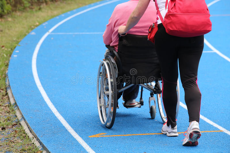 Mobility wheelchair on the athletic track during the sporting e. Senior with wheelchair on the athletic track during the sporting event stock photos
