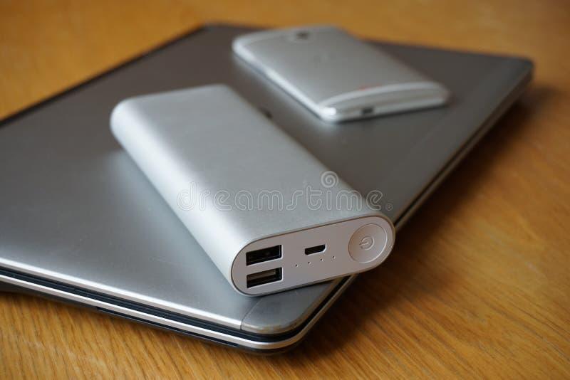 Mobilny biuro z aluminiowym laptopem, telefonem komórkowym i źródłem zasilania na drewnianym stole, (władza bank) obrazy royalty free