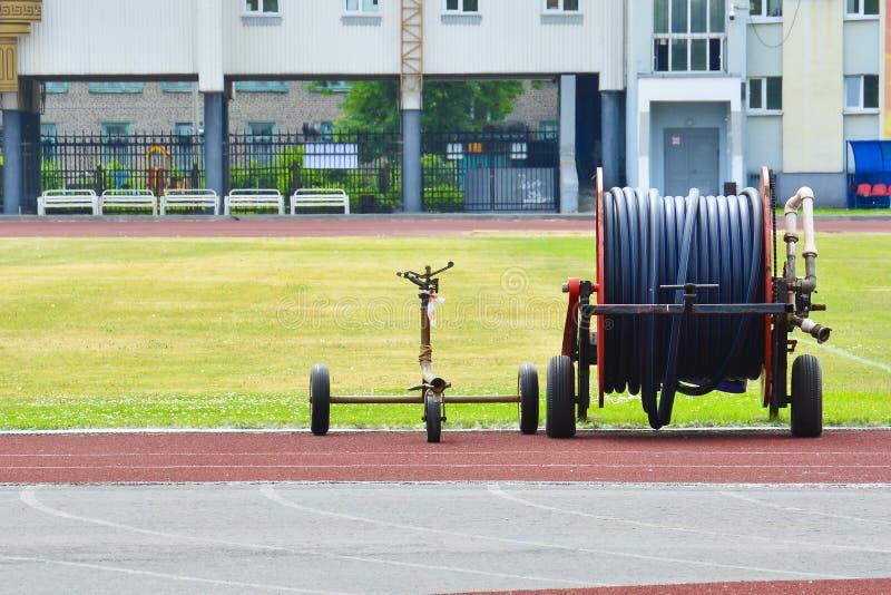 Mobilny kropidło na pustym zielonym boisku do piłki nożnej Duży bęben z wężem elastycznym dla nawadniać boisko piłkarskie zdjęcie royalty free