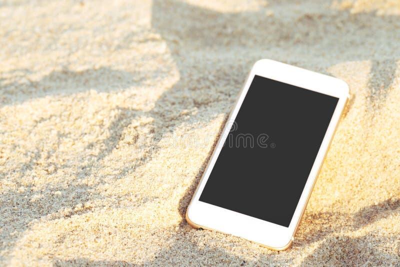 Mobilny mądrze telefon stawiający kropla na tropikalnej piasek plaży z światło słoneczne tekstury tłem pokazu czerni kopii przest fotografia stock