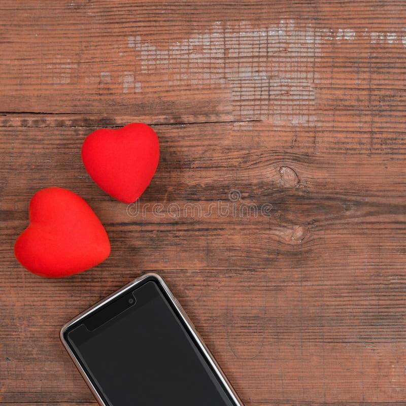 Mobilny mądrze telefon z czerń ekranem i dwa czerwonego serca na drewnianym textured tle, pusta kopii przestrzeń Mieszkanie nieat zdjęcia stock
