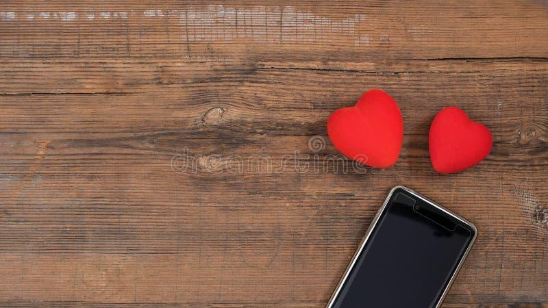 Mobilny mądrze telefon z czerń ekranem i dwa czerwonego serca na drewnianym textured tle, pusta kopii przestrzeń Mieszkanie nieat fotografia royalty free