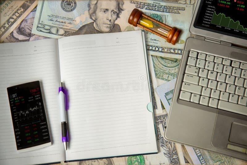 mobilny rynek otwarty ceny stół i pióro na nutowej książce odizolowywamy na dolarowych rachunków tle, laptopu rynku otwartego cen zdjęcie royalty free