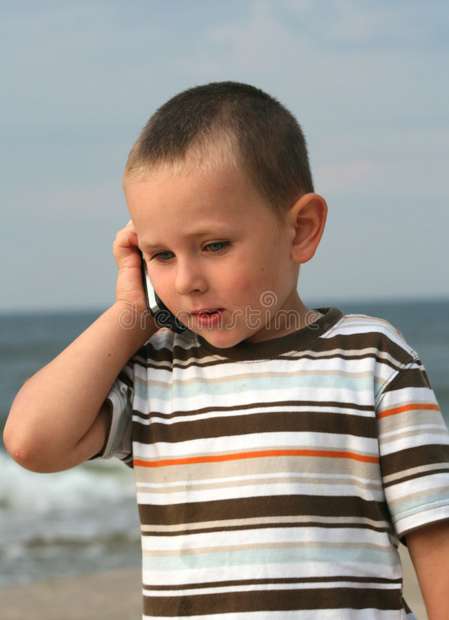 Mobilphone. Little boy using a mobile phone royalty free stock image