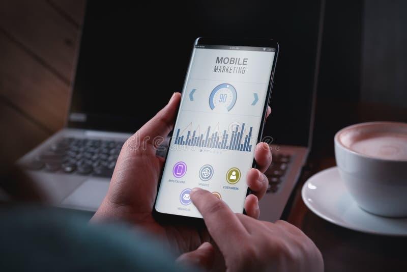 Mobilt begrepp för marknadsförings- och kunddataanalytics Tätt upp hand som två rymmer den smarta telefonen med mobil marknadsför arkivfoto