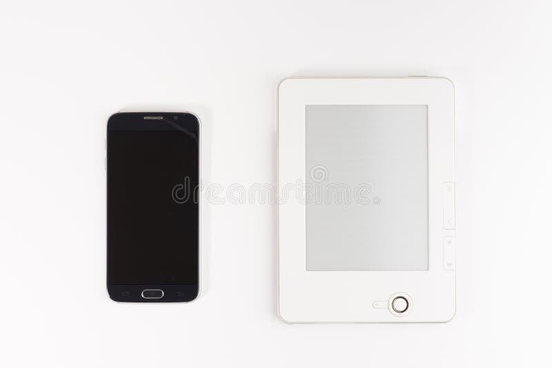 Mobilt läsning- och litteraturarkivbegrepp: bok med den tomma skärmen och pekskärmsmartphonen som isoleras på vit royaltyfri bild