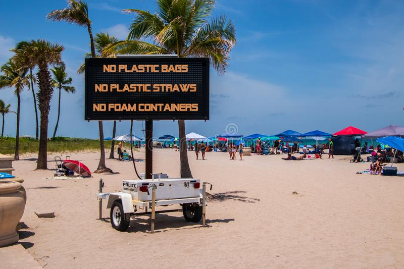 Mobilt tecken på stranden som säger, inga plastpåsar, inga plast- sugrör, inga skumbehållare arkivfoton