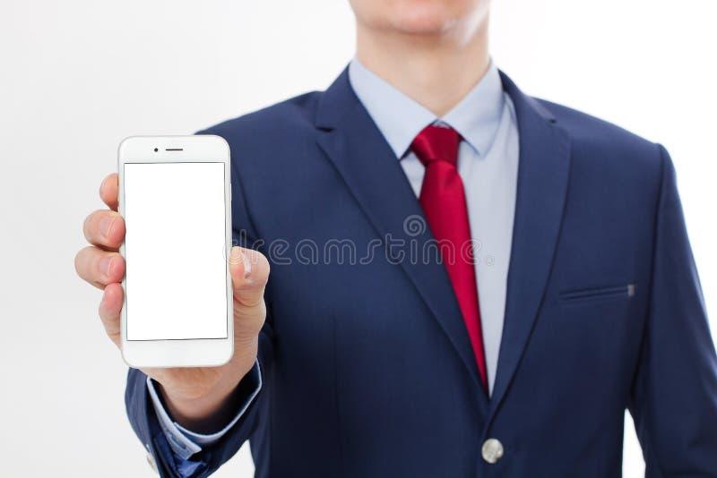 Mobiltelefon för affärsmaninnehav som och för tom skärm för visning isoleras på vit bakgrund Kopieringsutrymme och selektiv fokus arkivfoton