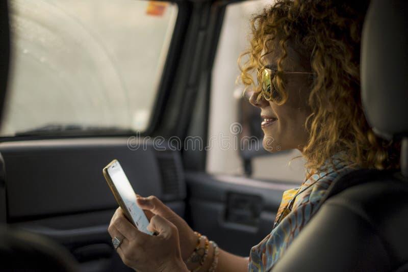 Mobiltelefon för kontroll för Eautiful mellersta ålderkvinna för hennes profil på socialt massmediastundlopp i en bil som passage royaltyfri bild