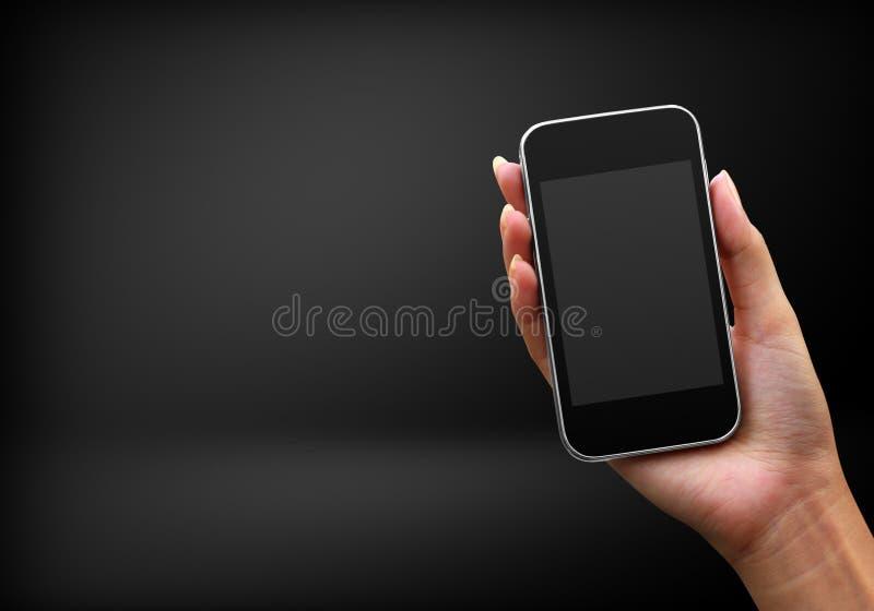 mobiltelefon för svart hand arkivfoto