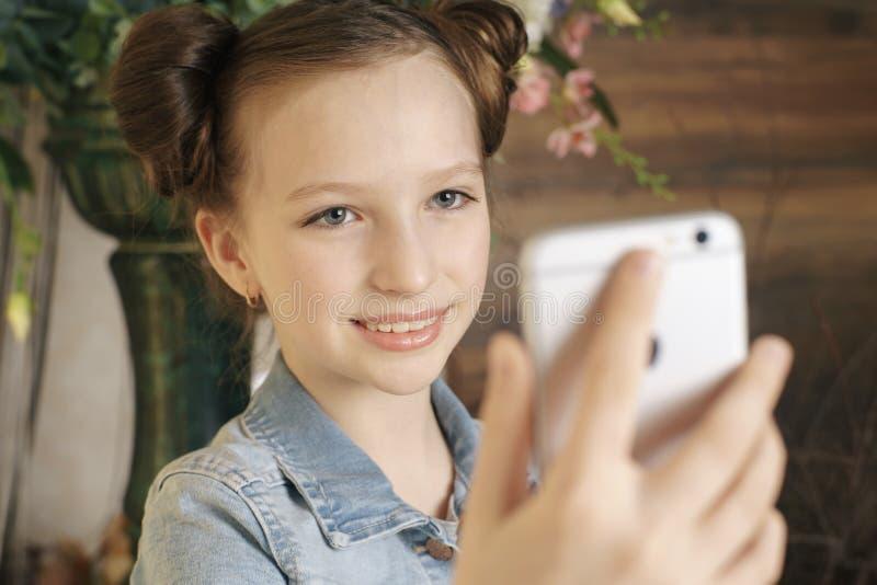 Mobiltelefon för tonårig flicka för skola hållande royaltyfri foto