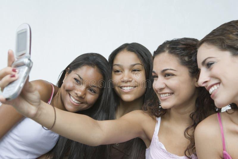 mobiltelefon fyra tonårs- flickor royaltyfri fotografi