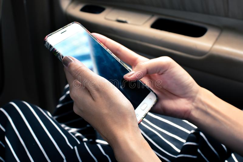 Mobiltelefon genom att använda, medan sitta i bil royaltyfri foto