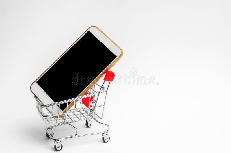 Mobiltelefon i en supermarketspårvagn köpa och sälja en smartphone Bärbar dator med markisen konsumentkreditering Isolerad vitbak royaltyfri bild