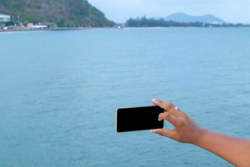 Mobiltelefon i hand med havet arkivfoto