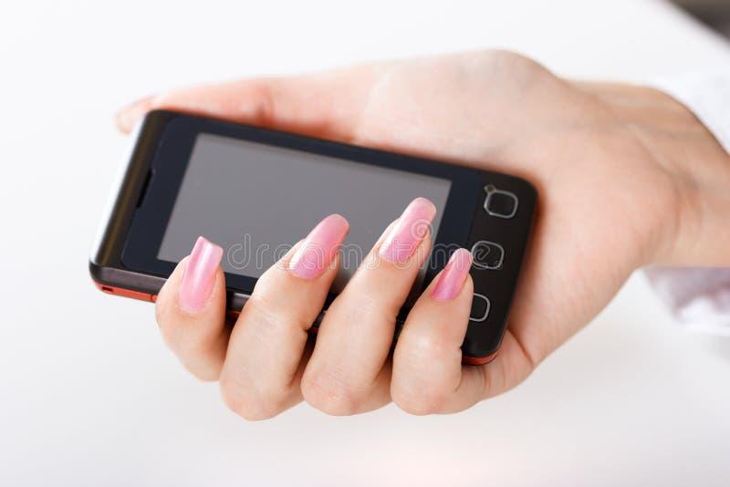 Mobiltelefon i kvinnahand royaltyfria bilder