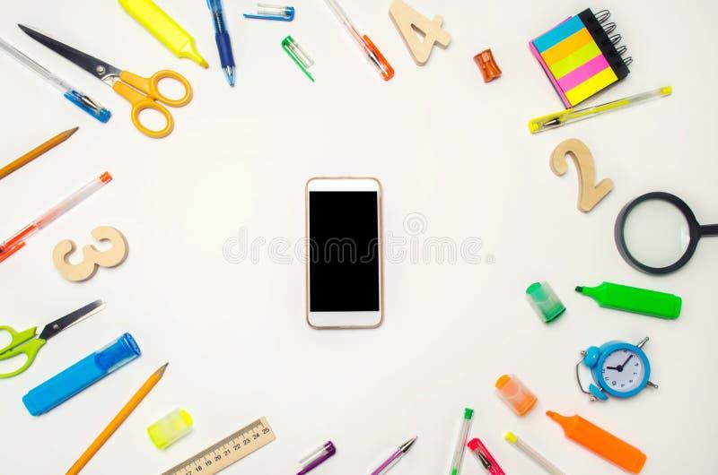 Mobiltelefon i skrivbordet Vit bakgrund äpplet books begreppsutbildningsred tillbaka skola till Idérik röra på skrivbordet Skrivb royaltyfria foton