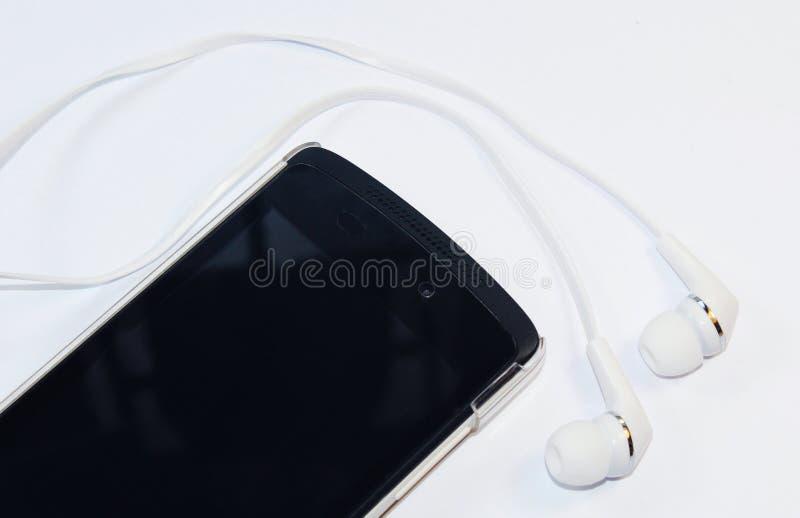 Mobiltelefon med öra-telefoner arkivfoton