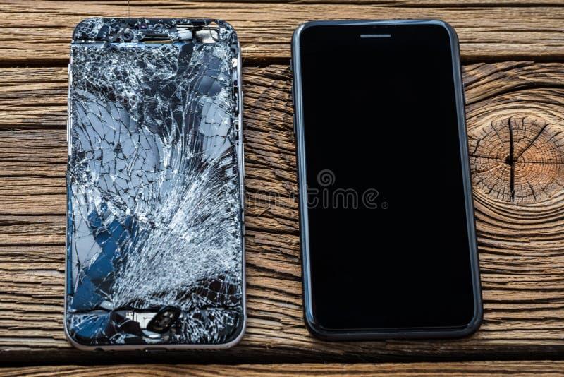 Mobiltelefon med den brutna pekskärmen på träbakgrund royaltyfria foton