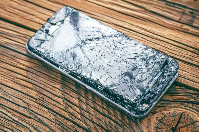 Mobiltelefon med den brutna pekskärmen på träbakgrund arkivfoto