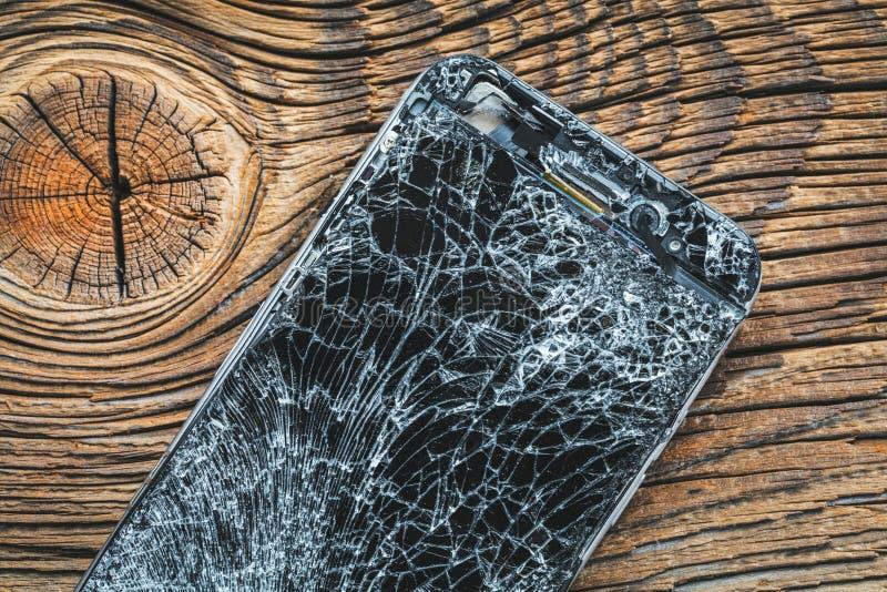 Mobiltelefon med den brutna pekskärmen på träbakgrund royaltyfri foto
