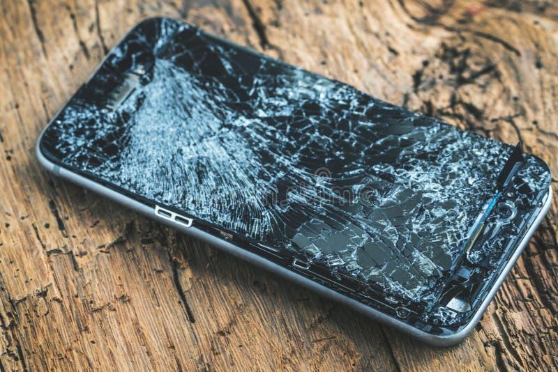 Mobiltelefon med den brutna pekskärmen på träbakgrund royaltyfri bild