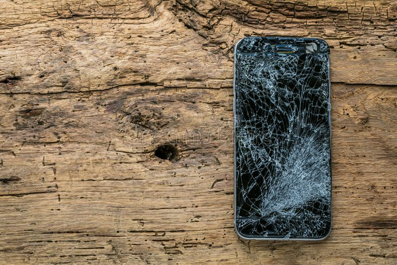Mobiltelefon med den brutna pekskärmen på träbakgrund arkivfoton