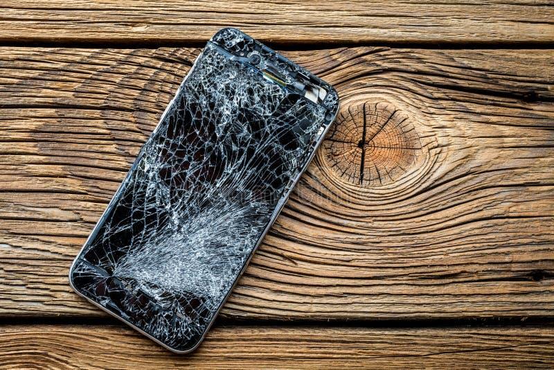 Mobiltelefon med den brutna pekskärmen på träbakgrund arkivbilder