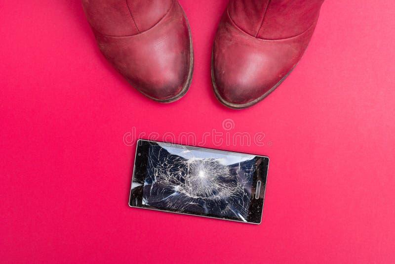 Mobiltelefon med den brutna skärmen på golv royaltyfri foto
