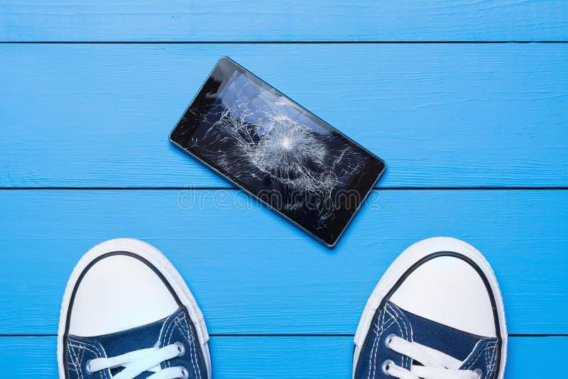Mobiltelefon med den brutna skärmen på golv royaltyfria bilder
