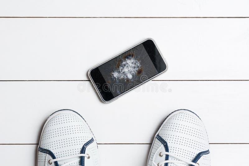 Mobiltelefon med den brutna skärmen på trägolv royaltyfria bilder