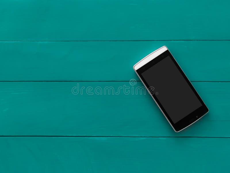 Mobiltelefon med den tomma skärmen på bakgrund för gräsplanblåttträtabell Smartphone på wood gammal plankatappningtextur royaltyfri bild