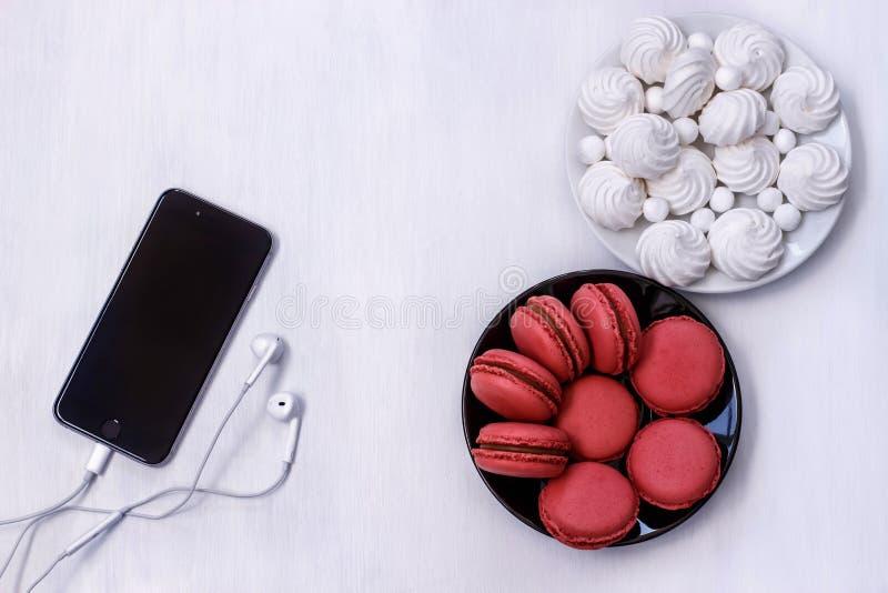 Mobiltelefon med hörlurar, makron och marängar på den vita tabellen fotografering för bildbyråer