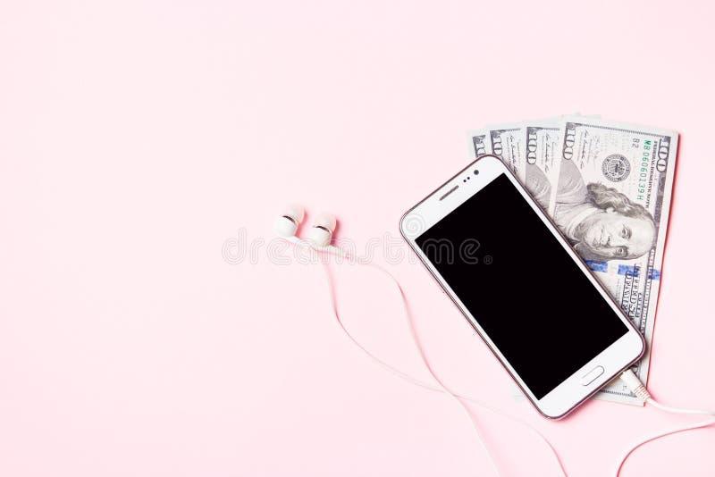 Mobiltelefon med hörlurar och pengar på rosa bakgrund Begrepp av betalning och besparingar royaltyfria foton