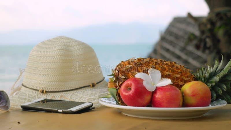 Mobiltelefon med hatten, solglasögon, frukter, frangipaniblomma för strandferie på havssiktsbakgrund i ön arkivfoto