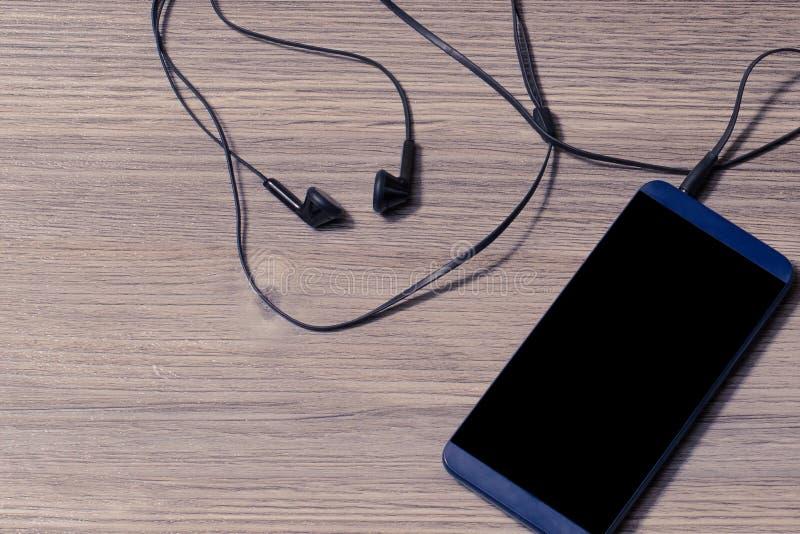 Mobiltelefon med svart hörlurar på begrepp för telefon för smartphone för mobiltelefon för hörlurar för lifetyle för vän för tabe royaltyfri fotografi