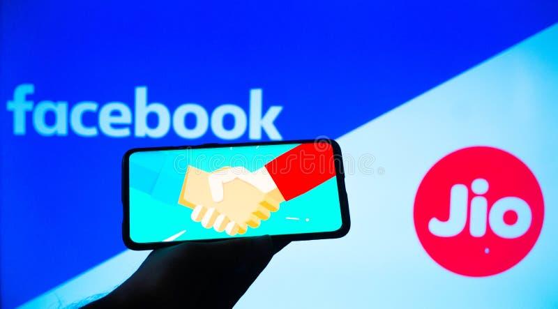Mobiltelefon mit Handshake-Bildschirm und Facebook und Jio im Hintergrund lizenzfreies stockfoto