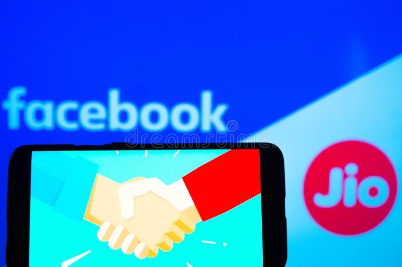 Mobiltelefon mit Handshake-Bildschirm und Facebook und Jio im Hintergrund lizenzfreie stockfotos