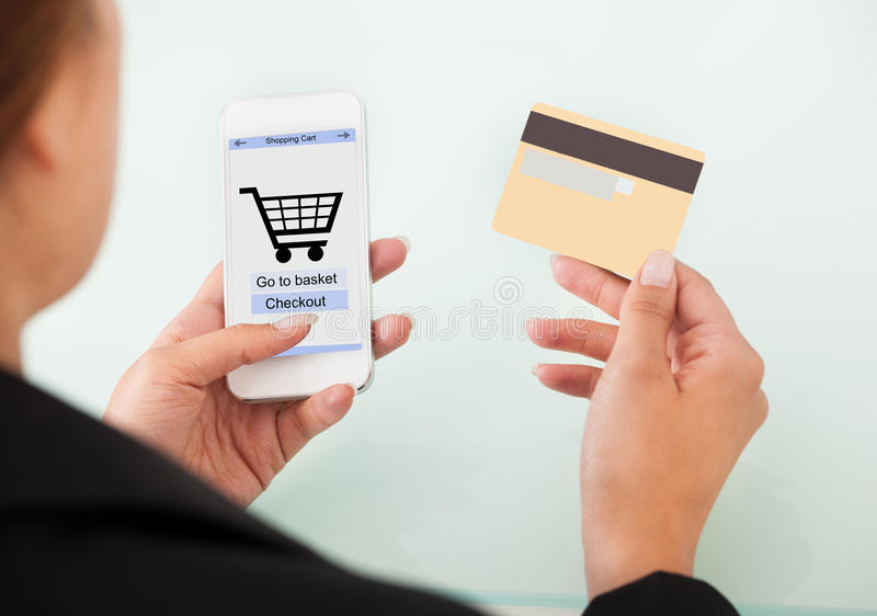 Mobiltelefon och kreditkort för affärskvinna hållande royaltyfri bild