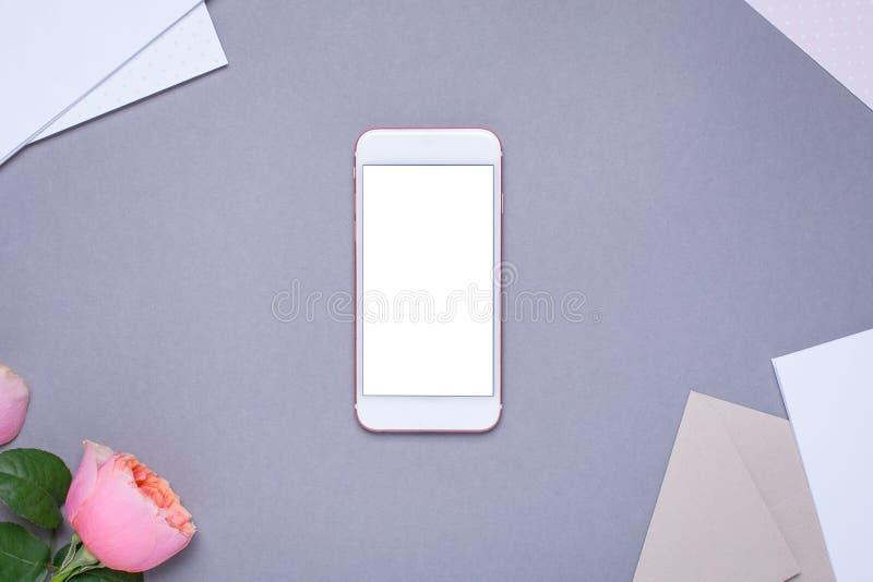 Mobiltelefon och kuvert med den rosa rosen på grå bakgrund royaltyfri foto