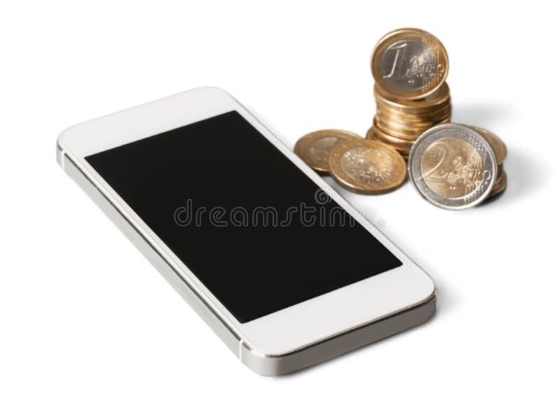 Mobiltelefon och mynt på vit bakgrund royaltyfria foton