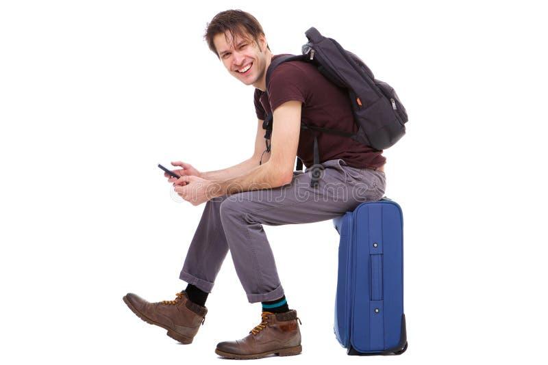 Mobiltelefon och sammanträde för full handelsresande för längd lycklig ung hållande på resväskan royaltyfria bilder