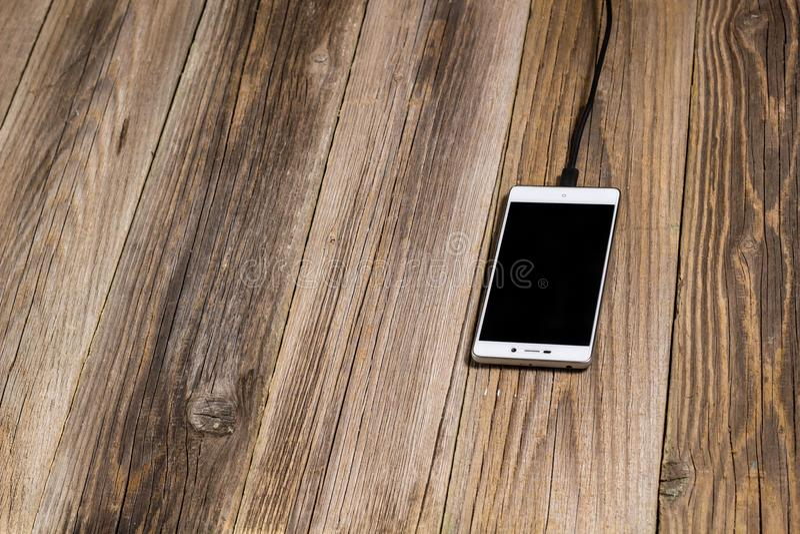 Mobiltelefon- och uppladdarekabel pluggade in på ett träskrivbord royaltyfri fotografi